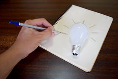 Man hand drawing a light bulb on note paper (idea concept) Stock Images