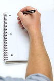 Man hand drawing in a notebook. Mans right hand drawing in a notebook Royalty Free Stock Images