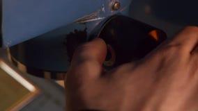 Man hand drukt kleine zwarte knoop op één of ander metaal mechanisch apparaat stock footage