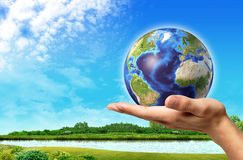 Man hand with Earth globe on it and a beautiful green landscape Royalty Free Stock Images
