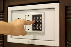 Man hand entering code on keypad of mini safe box Stock Photo