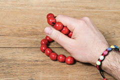 Man hand with female embellishments. Man hand with a female hand-made bracelet on his wrist holds red wooden beads Royalty Free Stock Photography