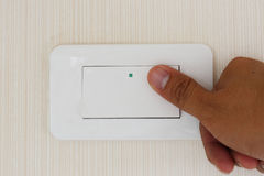 Man hand with finger on light switch, about to turn off the ligh Royalty Free Stock Images