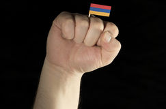 Man hand fist with Armenian flag isolated on black background Royalty Free Stock Photo