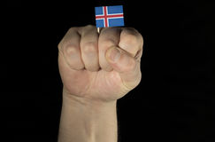 Man hand fist with Icelandic flag isolated on black background Stock Image