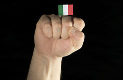 Man hand fist with Italian flag isolated on black background Royalty Free Stock Image