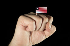 Man hand fist with Liberian flag isolated on black background Royalty Free Stock Photos