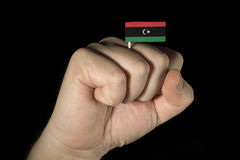 Man hand fist with Libyan flag isolated on black background Stock Photo
