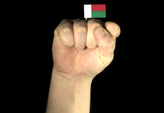 Man hand fist with Malagasy flag isolated on black background Stock Photos