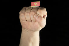 Man hand fist with Montenegrin flag isolated on black Stock Image
