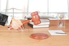 Man hand with gavel, books and hourglass on wooden table Royalty Free Stock Images