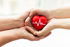 Man hand giving red heart to woman. Charity, health care, donation and medicine concept - men hand giving red heart with cardiogram to woman Royalty Free Stock Photos