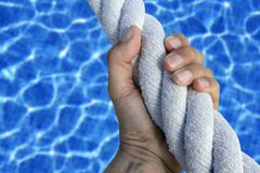 Man hand grab grip sport blue pool big rope Royalty Free Stock Photos