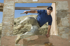 Man With Hand Gun Jumping Obstacle At Firing Range Stock Images