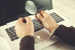 Man hand handcuffs and magnifier. On keyboard royalty free stock photos