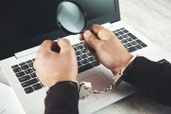 Man hand handcuffs and magnifier. On keyboard stock images
