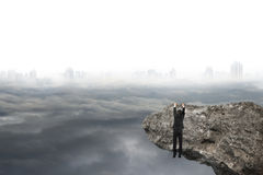 Man hand hanging on cliff with gray cloudy sky cityscape Royalty Free Stock Image