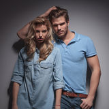 Man with hand in his hair leaning against girlfriend. Man with hand in his hair leaning against his girlfriend and posing in studio Royalty Free Stock Photos
