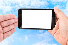 Man hand hold blank touch screen smart phone on blue sky Royalty Free Stock Photo