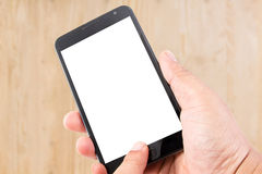 Man hand hold blank touch screen smart phone on wood texture Royalty Free Stock Photo