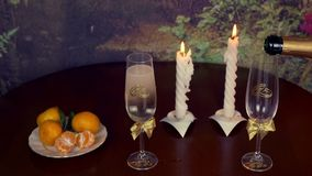 Man hand hold bottle of champagne wine and pour it to glasses. Wedding ring and glasses of champagne, and ornaments on. Black background. Valentine. Locked down stock video footage