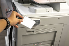 Man hand hold card for scanning key card to access  Photocopier Security system concept Royalty Free Stock Image