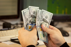 Man hand hold money on office background Stock Photos