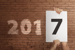 Man hand hold paper with number 7 on the wall 2017. New Year Concept Stock Photography