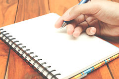 Man hand hold a pen writing on the notebook Royalty Free Stock Images