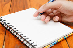 Man hand hold a pen writing on the notebook Stock Photos