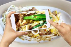 Hand Hold a Smart Phone take a Photo of Pad Thai Noodle Fire stock photos