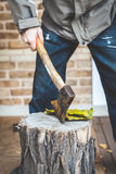 Man hand holding ax, which juts out into stump Royalty Free Stock Photo