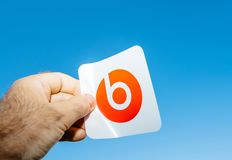 Man hand holding Beats by Dr Dre stocker manual blue sky background. Paris, France - Jun 17, 2019: Man hand holding red sticker with logotype insignia brand stock photography