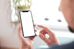 Man hand holding the black smartphone with big blank screen and modern frame less design royalty free stock photography