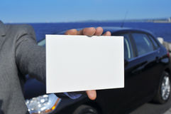 Man hand holding a blank signboard with a car in the background Royalty Free Stock Photography