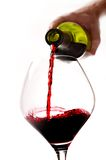 Man Hand holding Bottle filling Glass with Red Wine Stock Photo