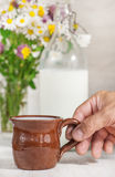 Man hand holding ceramic mug with milk Stock Photo