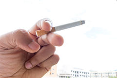 Man hand holding a cigarette with smoke Stock Photos