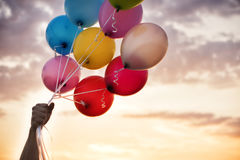 Man Hand Holding Colorful Balloons And A Beautiful Sunset. Birthday Party Balloons. Man Hand Holding Colorful Balloons And A Beautiful Sunset. Birthday Party royalty free stock image