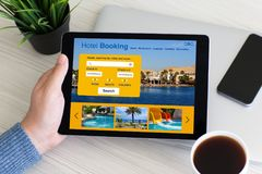 Man hand holding computer tablet with app hotel booking screen Stock Photography