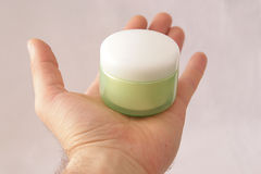 Man hand holding a container. Full of cream Royalty Free Stock Photo