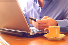 Man hand holding credit card next to laptop and cup of coffee. online shopping concept. retro style image. selective focus Stock Photos