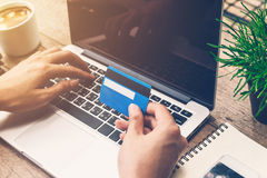 Man hand holding credit card and using laptop. Online payment. Royalty Free Stock Image
