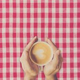 Man hand holding cup coffee on red and white fabric. Stock Image