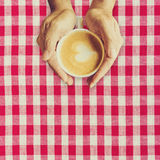 Man hand holding cup coffee on red and white fabric. Royalty Free Stock Photos