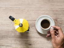 Man hand holding Cup of coffee and Yellow coffee maker kettle o Royalty Free Stock Images