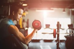 Man hand holding dumbbell exercise in gym. Fitness muscular body with set of black weights in the gym background. Exercise and healthy lifestyle concept royalty free stock image