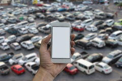 Man hand holding empty screen of smart phone and Outdoor parking Royalty Free Stock Images