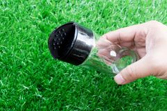 Man hand holding empty transparent glass bottle of pepper. Above artificial grass royalty free stock images