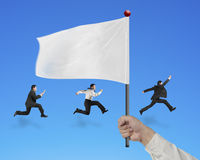 Man hand holding flag with businessmen running  on blue Royalty Free Stock Photos